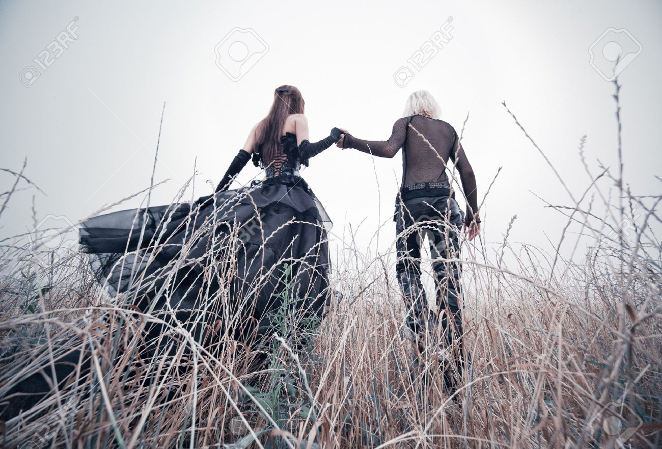 7677858-young-goth-couple-walking-on-field-bright-white-colors